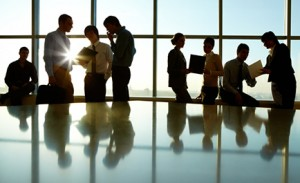 Business People Discussing Documents by Window
